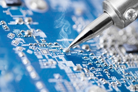 components: Microcircuit being fixed with soldering iron - very sharp micro photo