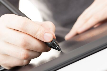 Artist drawing something on graphic tablet with pen photo