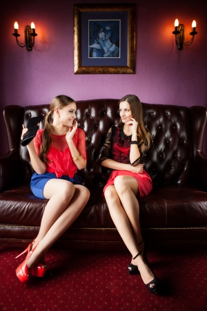 Two attractive ladies sitting on sofa photo