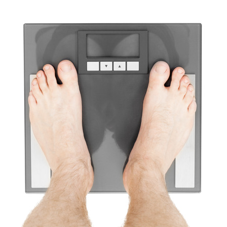 overeat: Man standing on weight scales with bare foot - view from top