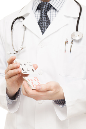 Doctor holding poker playing cards as a gambling with your health or curing gambling addiction photo