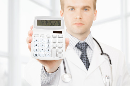 Medical doctor with a calculator in his righ hand showing calculated costs and revenues in physician practice and hospital fees photo