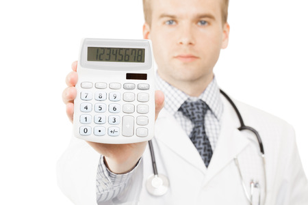 Medical doctor isolated on white with a calculator in his right hand showing calculated costs and revenues in physician practice and hospital fees photo