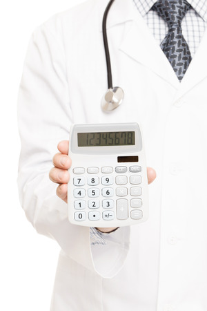 Medical doctor with a calculator in his right hand showing calculated costs and revenues in physician practice and hospital fees photo