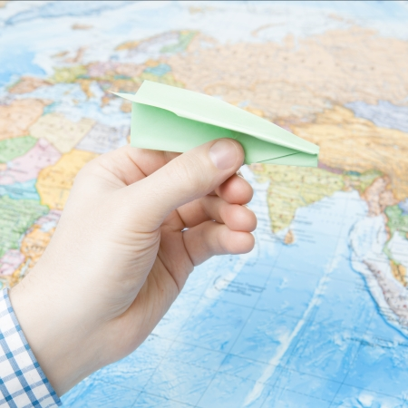 Male holding paper plane in hand with world map on  photo