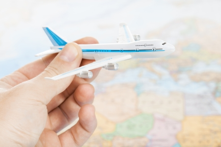 Toy plane in hand with world map on  photo