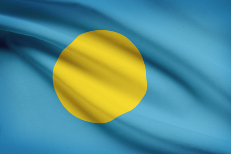 Palauan flag blowing in the wind. Part of a series. photo