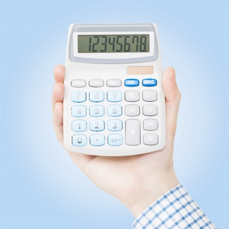 Male hand holding calculator on blue background photo