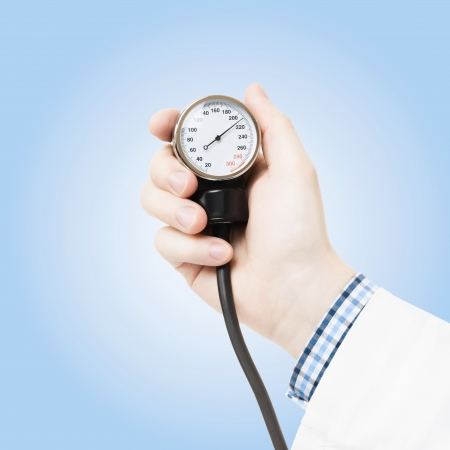 Doctor holding blood pressure measuring tool on blue background photo