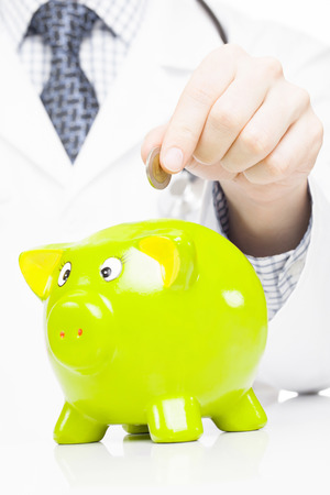 medical expenses: Doctor with green piggy bank as an idea for healthcare insurance and savings for medical expenses