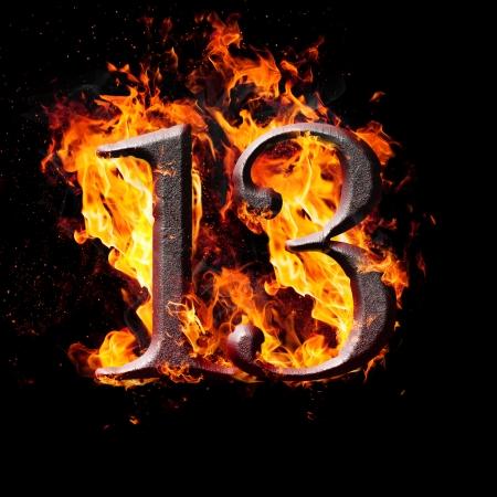 Hot metal burning numbers on black background - number thirteen photo