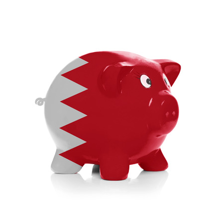 bahrain money: Piggy bank with flag coating over it isolated on white - Bahrain