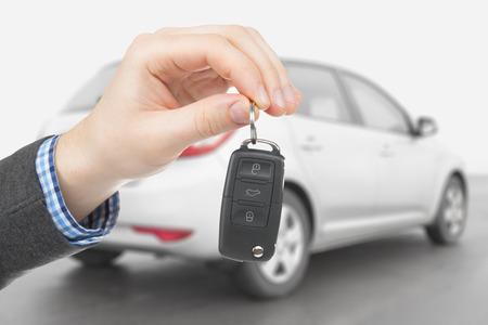 背景に車と車のキーを保持している男性 写真素材