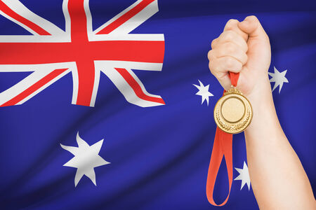 Sportsman holding gold medal with flag on background - Australia photo