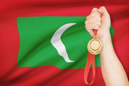 medalist: Sportsman holding gold medal with flag on background - Maldives