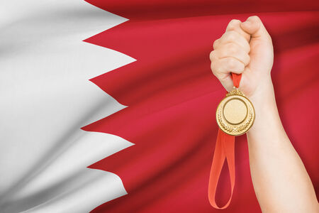 Sportsman holding gold medal with flag on background - Kingdom of Bahrain photo