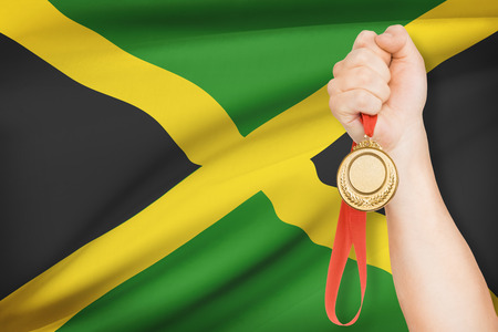 parliamentary: Sportsman holding gold medal with flag on background - Jamaica Stock Photo