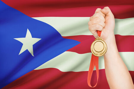 puerto rican flag: Sportsman holding gold medal with flag on background - Commonwealth of Puerto Rico