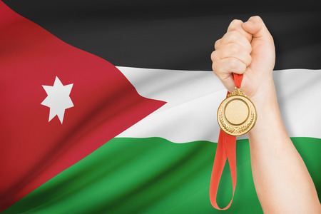 the hashemite kingdom of jordan: Sportsman holding gold medal with flag on background - Hashemite Kingdom of Jordan