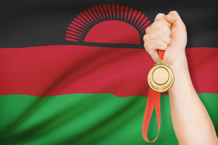malawian flag: Sportsman holding gold medal with flag on background - Republic of Malawi