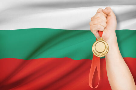 Sportsman holding gold medal with flag on background - Republic of Bulgaria photo