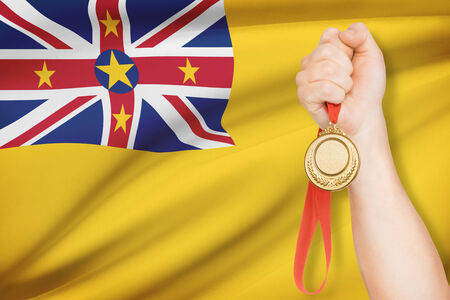 niue: Sportsman holding gold medal with flag on background - Niue