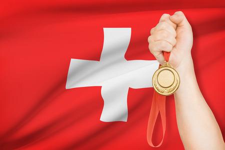 confederation: Sportivo tenendo medaglia d'oro con bandiera su sfondo - Confederazione svizzera Archivio Fotografico