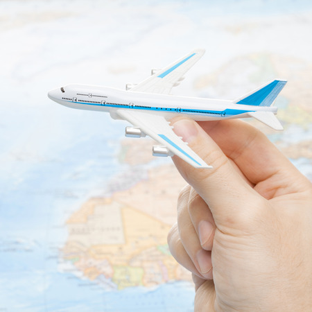 Toy aircarft in hand with world map on background with focus on the plane photo