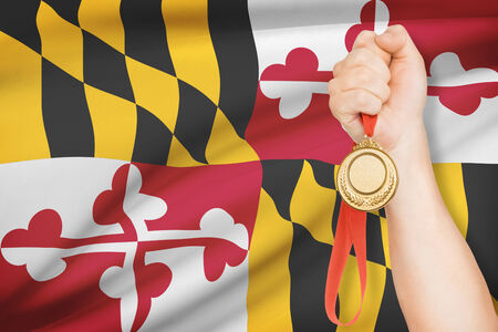 maryland flag: Sportsman holding gold medal with State of Maryland flag on background. Part of a series.