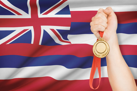 hawaii flag: Sportsman holding gold medal with State of Hawaii flag on background. Part of a series.