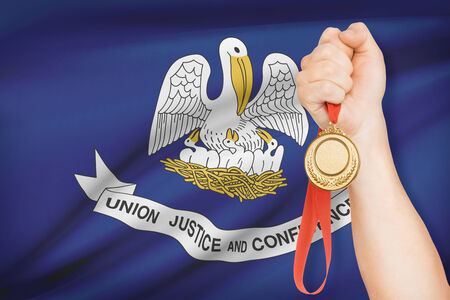 louisiana flag: Sportsman holding gold medal with State of Louisiana flag on background. Part of a series.