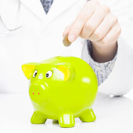 medical expenses: Medical doctor putting a coin into piggy bank as an idea for healthcare insurance and savings for medical expenses