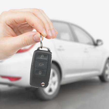 Male holding car keys with car on background - 1 to 1 ratio photo