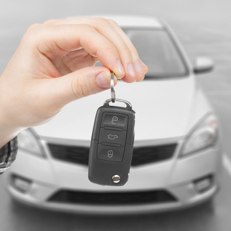 Male holding car keys with parked car on background - 1 to 1 ratio Stock Photo