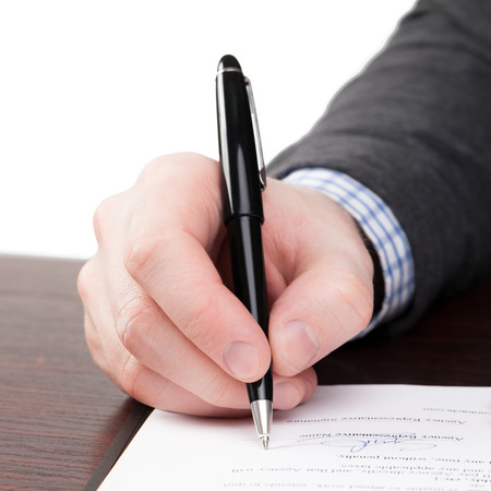 Male signing documents with black pen on a desk - 1 to 1 ratio