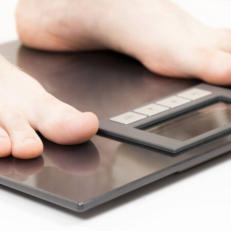 overeat: Man standing on weight scales with bare foot - 1 to 1 ratio