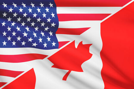 Flags of USA and Canada blowing in the wind. Part of a series. photo