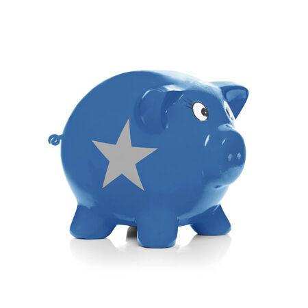 buying stock: Piggy bank with flag coating over it isolated on white - Somalia Stock Photo