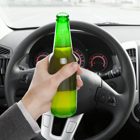 hard drive crash: Male hand holding bottle of beer while driving car