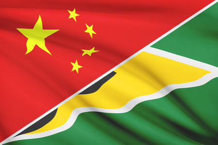 cooperativa: Banderas de China y la Rep�blica Cooperativa de Guyana en el viento. Parte de una serie.