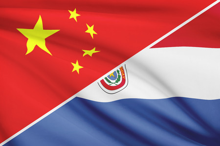 Flags of China and Republic of Paraguay blowing in the wind. Part of a series. photo