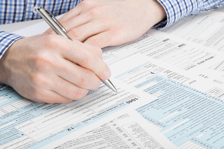 taxable: Tax Form 1040 - man performing tax calculations