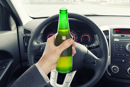 hard drive crash: Man holding bottle of beer while driving car