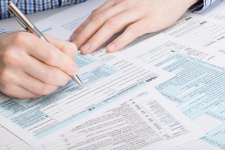 federal tax return: US 1040 Tax Form - male filling out tax form