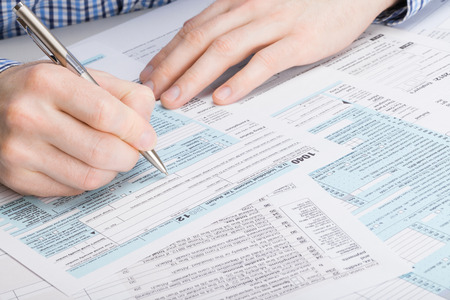 US 1040 Tax Form - male filling out tax form