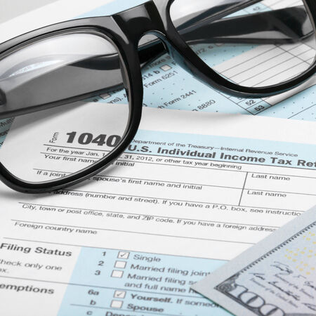 taxable income: Tax Form 1040 with dollars and glasses