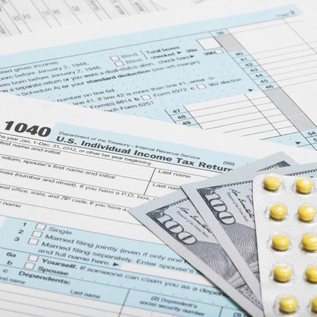taxable: Tax Form 1040 with dollars and pills  Stock Photo