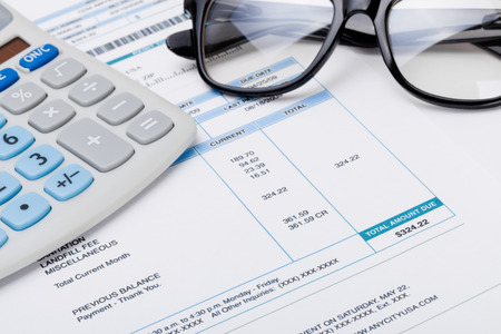 utility payments: Studio shot of calculator and glasses over some receipt Stock Photo
