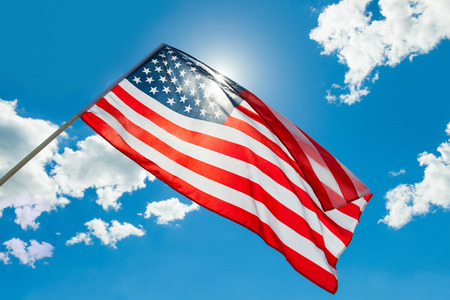 red america: USA flag waving on blue sky background