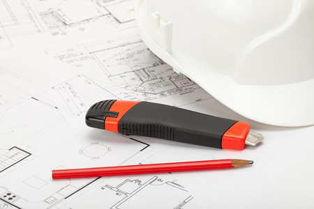 box cutter: White construction helmet with pencil and box cutter knife above blueprint